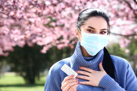 Young woman with antihistamine pills wearing protective mask near blooming tree Stock Photo