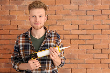 Handsome plumber with sealant near brick wall