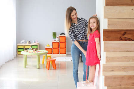 Young mother measuring height of her little daughter at home Imagens
