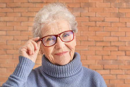 Portrait of senior woman on brick background