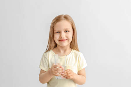 Cute little girl with glass of water on light background