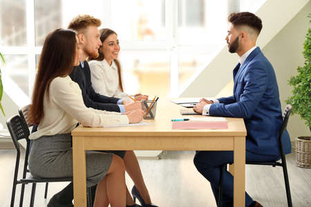 Human resources commission interviewing man in office Imagens