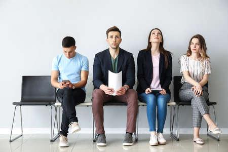 Young people waiting for job interview indoors Foto de archivo