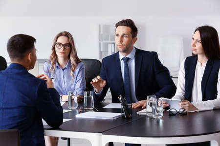 Human resources commission interviewing man in office Stock Photo