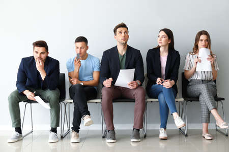 Young people waiting for job interview indoors Stock Photo