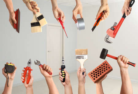 Many hands with different construction tools indoors