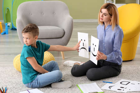 Female psychologist working with boy suffering from autistic disorder