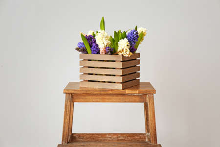 Box with beautiful hyacinth flowers on table