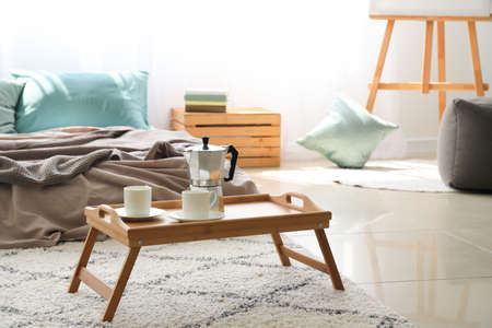 Small table with coffee pot and cups in stylish bedroom