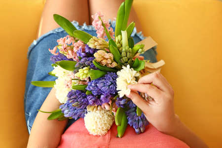 Woman with beautiful hyacinth flowers at home