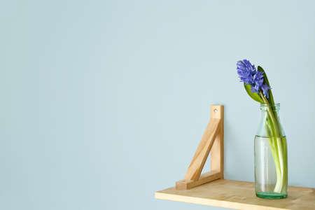 Bottle with beautiful hyacinth flowers on shelf