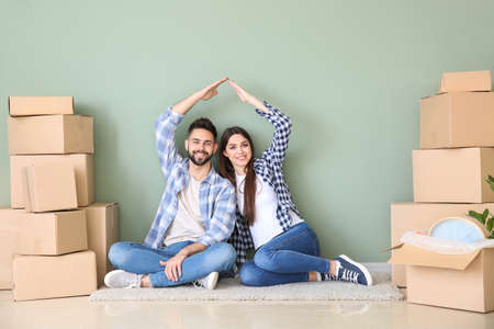 Young couple with belongings sitting near color wall in their new house