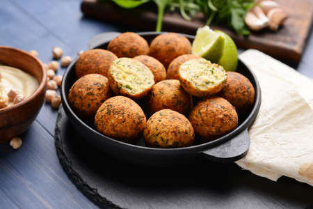 Frying pan with tasty falafel balls on table