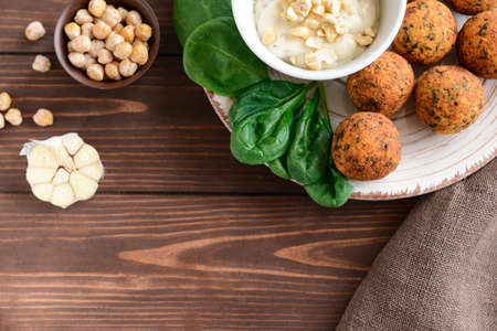 Plate with tasty falafel balls and sauce on wooden table Stok Fotoğraf - 163657928