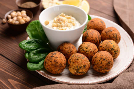 Plate with tasty falafel balls and sauce on wooden table Stok Fotoğraf - 163657548