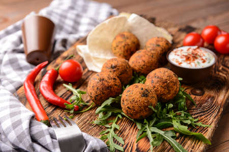 Tasty falafel balls and sauce on wooden board