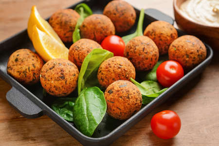 Frying pan with tasty falafel balls on wooden table Stok Fotoğraf - 163657285