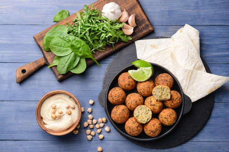Frying pan with tasty falafel balls and sauce on wooden table