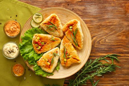 Plate with delicious vegetable samosas and sauces on wooden table Stok Fotoğraf - 163657781