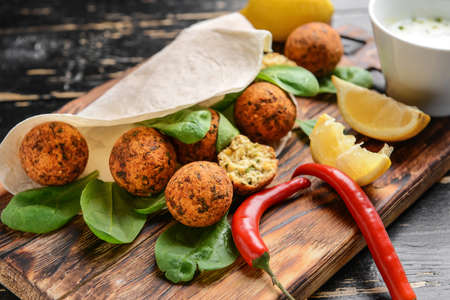 Tasty falafel balls with flatbread and spinach on wooden board