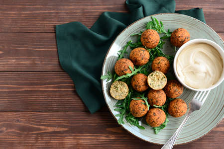 Plate with tasty falafel balls and sauce on wooden table
