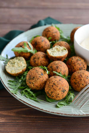 Plate with tasty falafel balls on wooden table, closeup