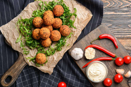 Tasty falafel balls and sauce on wooden table