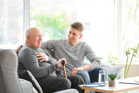 Male caregiver with senior man in nursing home