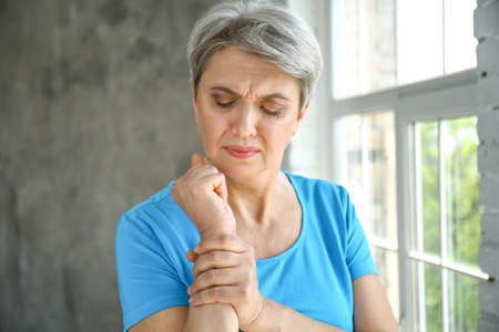 Mature woman suffering from pain in wrist at home