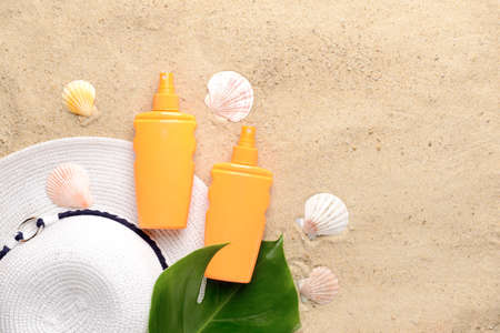 Bottles of sun protection cream, hat and seashells on sand