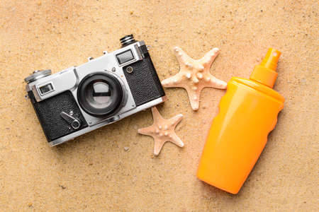 Bottle of sun protection cream, starfishes and photo camera on sand