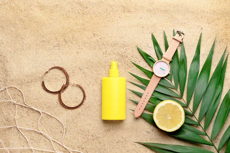 Bottle of sun protection cream and female accessories on sand 版權商用圖片