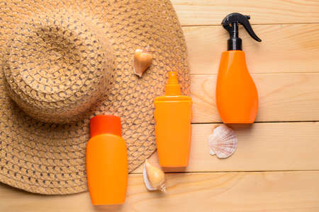 Bottles of sun protection cream, hat and seashells on wooden background 版權商用圖片