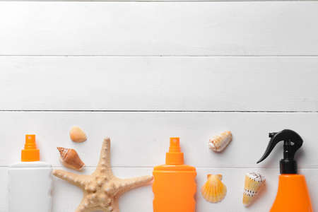 Bottles of sun protection cream and seashells on wooden background 版權商用圖片