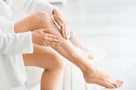 Beautiful young woman applying body scrub at home Reklamní fotografie