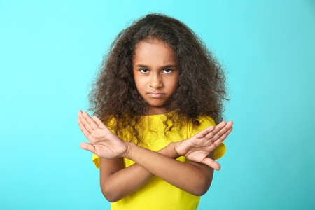 Cute African-American girl rejecting something on color background
