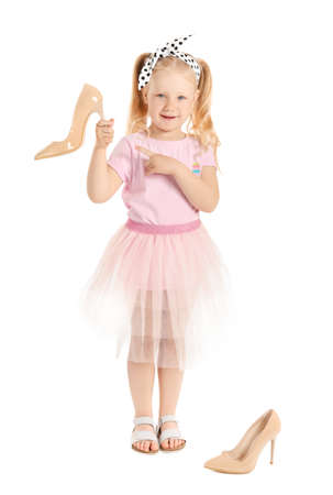 Portrait of adorable little girl with mother's shoes on white background