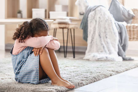 Crying little African-American girl at home