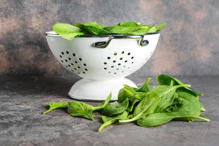 Colander with fresh spinach on grunge background