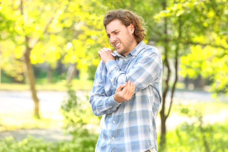 Young man suffering from pain in elbow outdoors