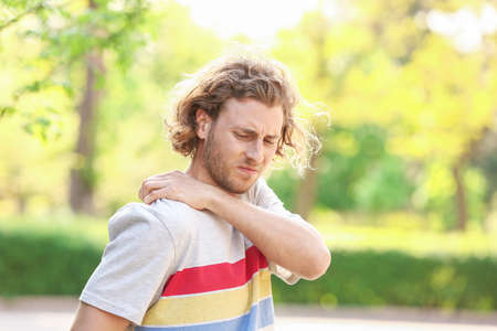Young man suffering from pain in shoulder outdoors