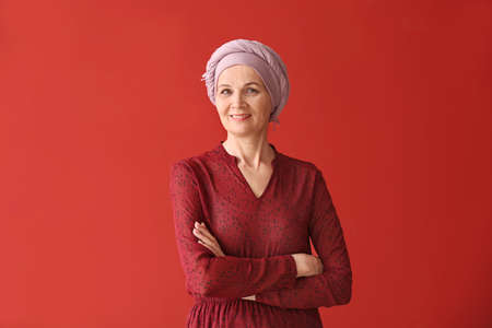 Mature woman after chemotherapy on color background