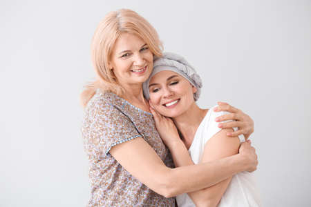 Woman after chemotherapy with her mother on light background