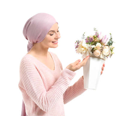 Woman after chemotherapy with bouquet of flowers on white background