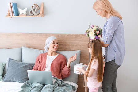 Family greeting woman after successful treatment at home
