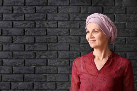 Mature woman after chemotherapy on dark brick background