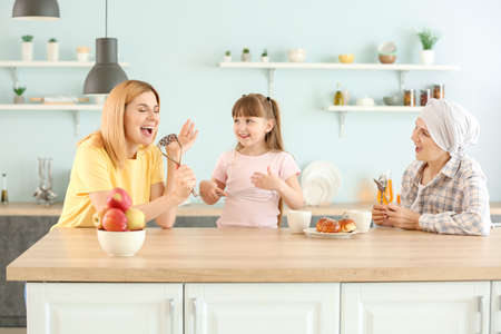 Mature woman after chemotherapy with her family having fun in kitchen at home