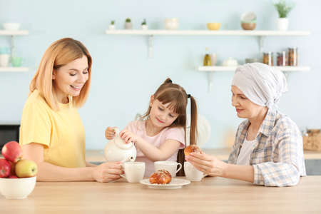 Mature woman after chemotherapy with her family in kitchen at home