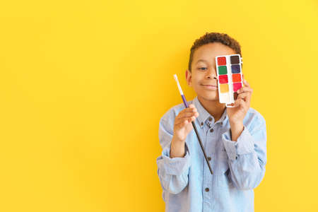 Cute little African-American artist on color background