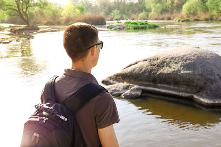 Male tourist near river with rocks